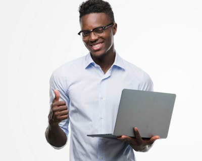 a man smiling while holding a laptop