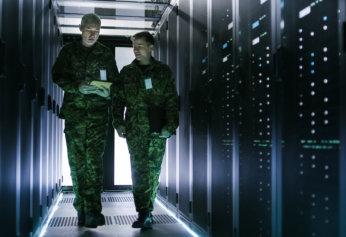 Two Military Men Walking in Data Center Corridor.